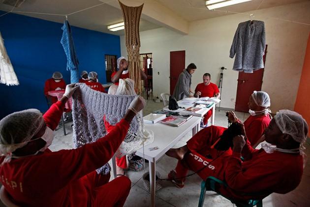 Raquel Guimaraes (centre, standing) supervises prisoners knitting for her