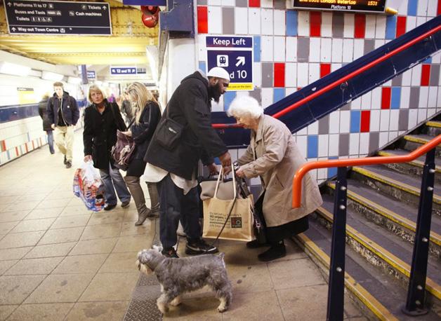 2. Um homem ajuda a senhora com suas sacolas no metrô.