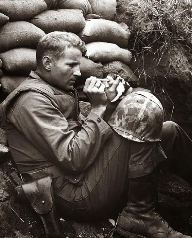 6. Essa é das antigas! Soldado alimenta filhote de gato em meio à trincheira.