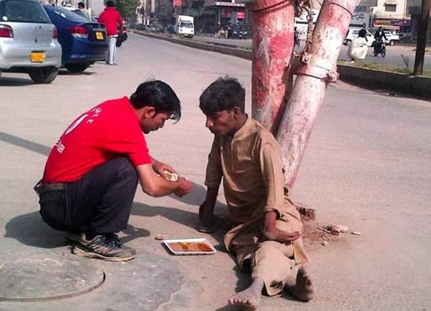 12. O comerciante dá comida ao deficiente físico.
