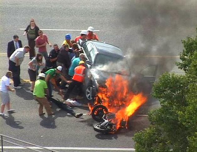 13. Pessoas removem o carro que estava em cima de um motociclista.
