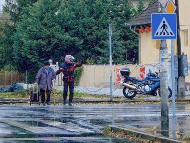 15. O rapaz estacionou a moto para poder ajudar uma senhora a atravessar a rua.