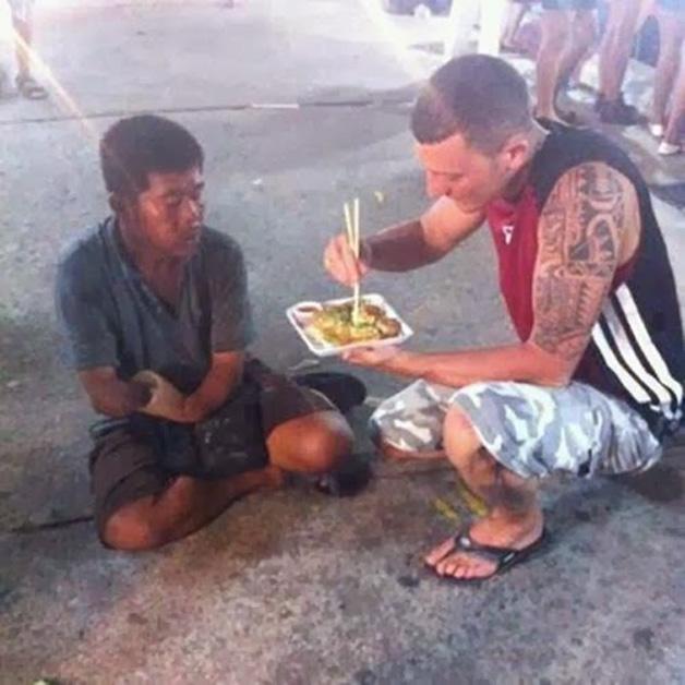 16.  Desconhecido ajuda rapaz sem as mãos a se alimentar
