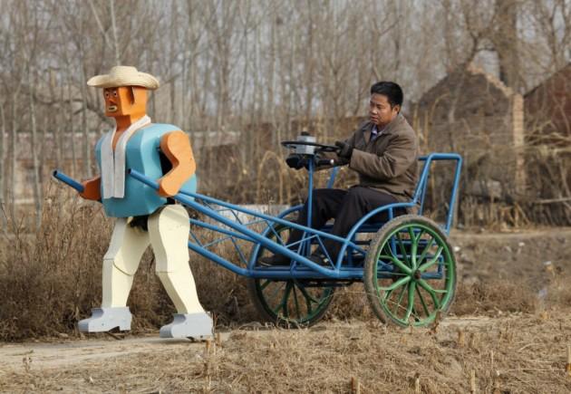 Wu Yulu dirige seu riquixá puxado por um robô andante.
