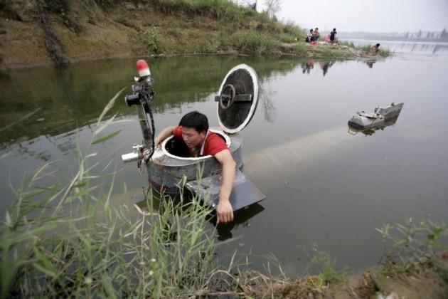 """No melhor estilo """"Chaves"""", Tao Xiangli navega com seu barril submarino em Pequim."""