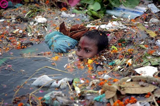 Menino nadando em água poluída na Índia