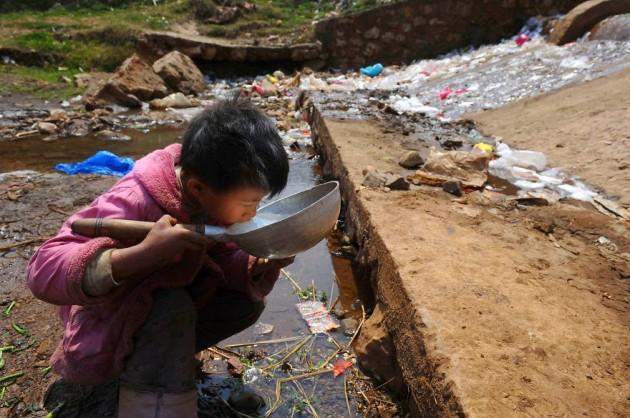 Criança bebendo água de um lixão na China
