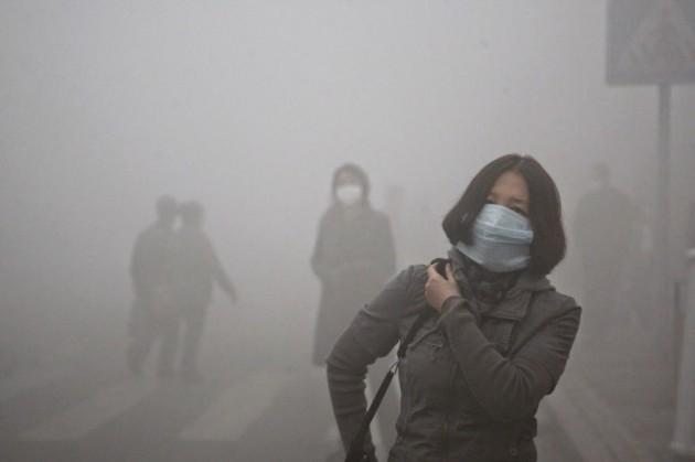 Mulher anda pelas ruas de Pequim, onde a poluição por partículas pequenas excedeu 40 vezes à norma de segurança internacional