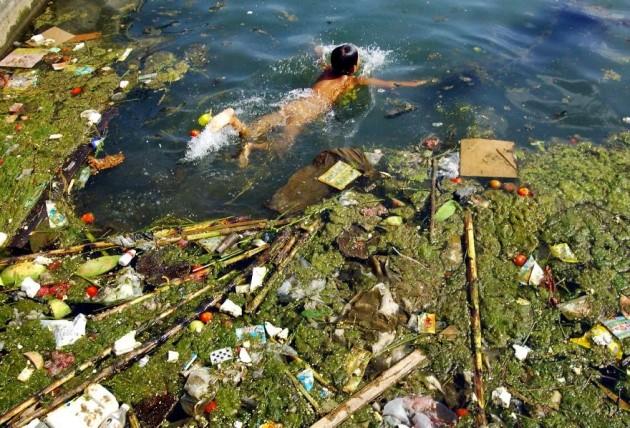 Criança nada em água de lixo e poluída na China