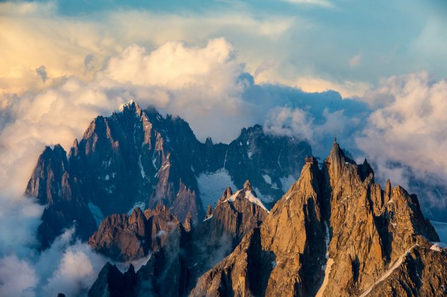 A wide-angle view on Aiguille du Midi and Aiguille Verte during a spectacular alpenglow in Chamonix Valley. Photograph taken on a warm and stormy Summer afternnon from Aiguille Gouter.