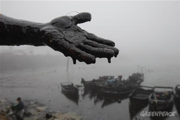 The oil covered hand of a local fishermen who is cleaning up oily sludge from the contaminated beaches at Nanhaitun, Weitang Bay. The spill was caused by a pipeline blast.