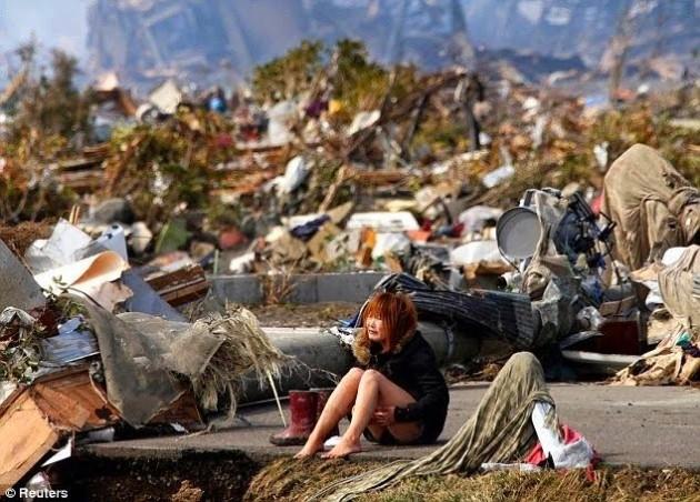 Mulher abalada após o terremoto/tsunami no Japão em 2011.