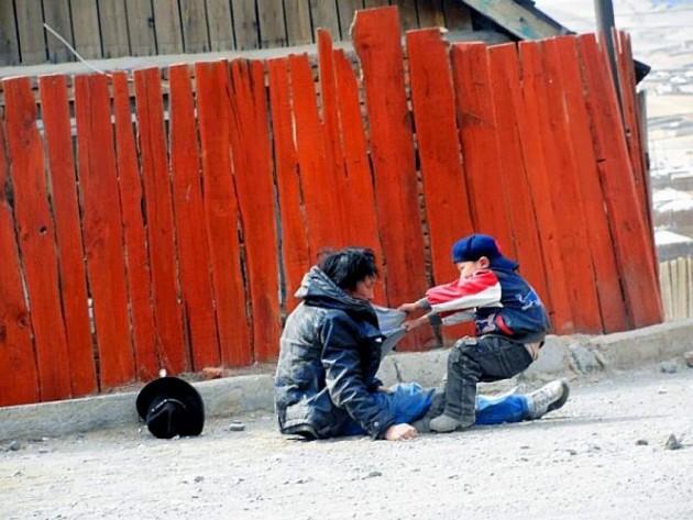 Criança tentando acordar o pai alcoolizado.