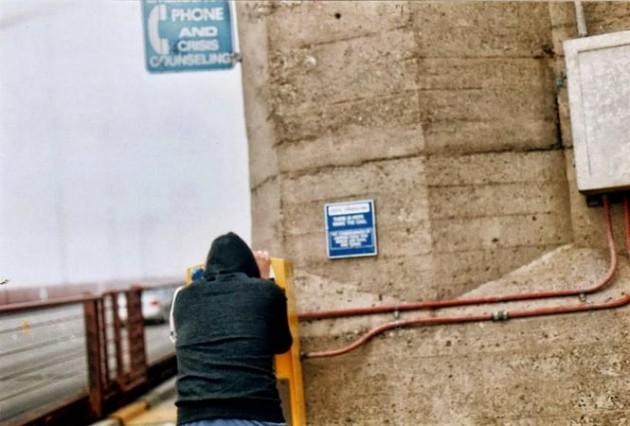 Homem usando a linha do suicídio na ponte Golden Gate, local onde mais se comete suicídios no mundo. Esse telefone foi ali instalado para quando uma pessoa prestes a se matar quer ajuda antes de tirar a vida.