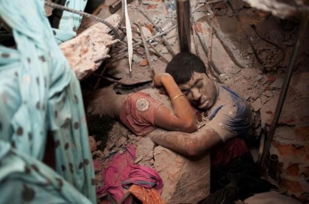 Casal abraçado em escombros de fábrica que desabou.