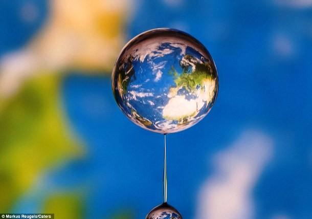 Gota d'água refletindo o mapa-mundi no fundo da foto